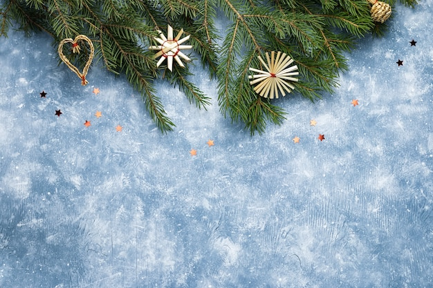 Christmas border with pine, wooden ornaments on blue