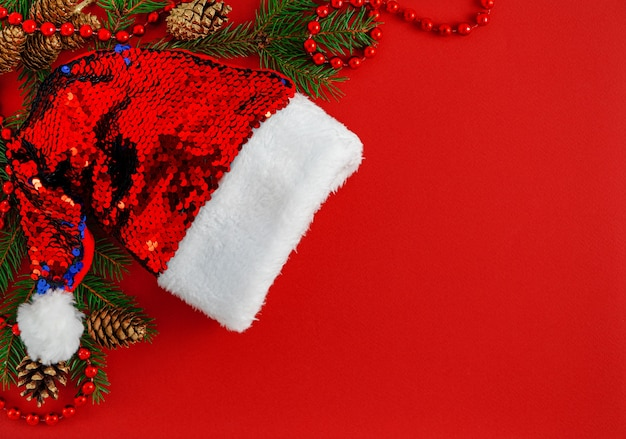Christmas border with santa hat on red background.