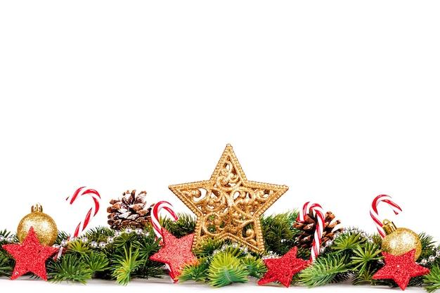 Рождественская граница с ветвями деревьев с золотыми шарами, конфетами и большой звездой