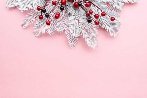 パステルピンクの背景に白いモミの枝と赤い果実とクリスマスの境界線