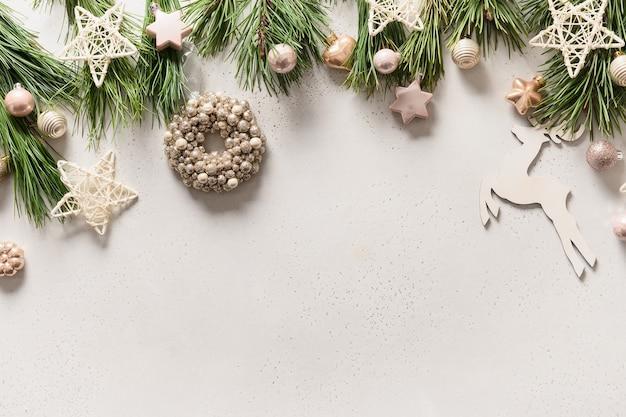 Рождественская граница с белым венком, звездами, шарами, снежинками, оленями, вечнозелеными ветвями на белом.