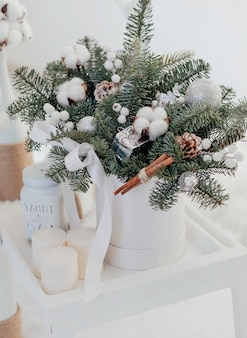 Christmas bouquet of spruce and cotton in a white interior. happy new year.