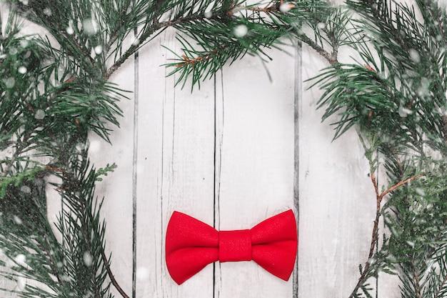 Украшение бабочки рождества с снегом на белой деревянной предпосылке.