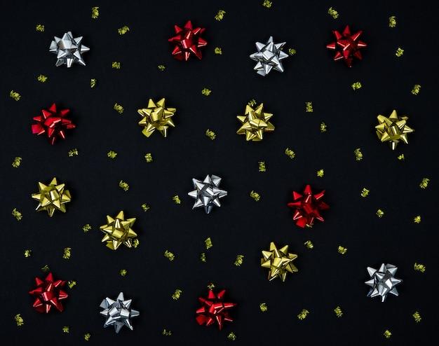 Рождественские банты для украшения на черном фоне. вид сверху. плоская планировка.
