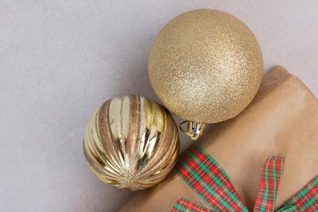 회색 테이블에 황금 공이 있는 크리스마스 상자