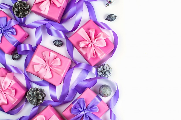 Christmas boxes with gifts on the occasion of pink color on white background cones nuts decor
