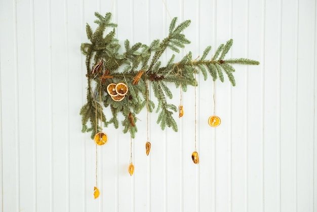 Christmas branch of dried lemons with fir tree on wooden background