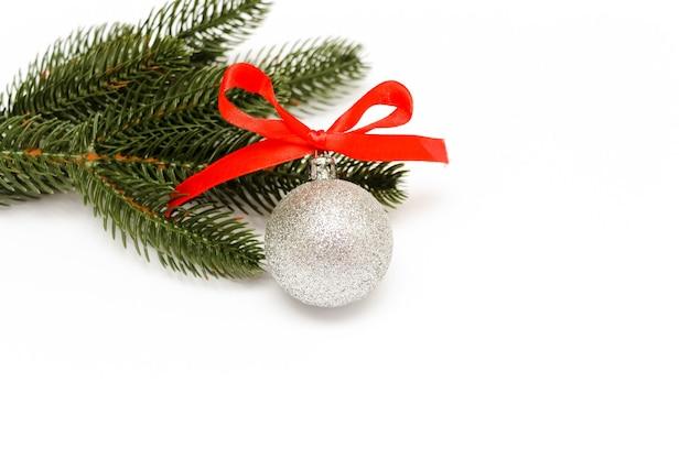 Рождественская ветвь сосны и серебряный шар на белом фоне. новогодняя открытка