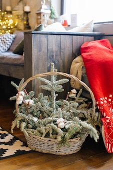 Christmas branches of fir or spruce in a composition with cotton in a wicker basket used as a decor in the house