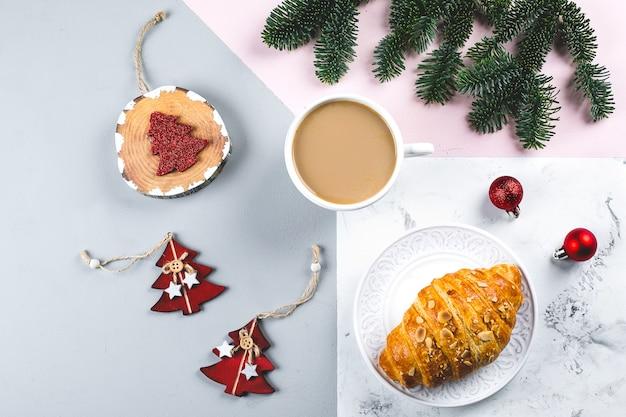 クリスマスの朝食。一杯のコーヒー、クロワッサン、休日の装飾のおもちゃ、三色のテーブルに木のモミの枝。バックグラウンド。平面図、平置き