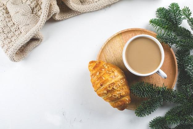 クリスマスの朝食。一杯のコーヒー、クロワッサン、休日の装飾のおもちゃ、白いテーブルの上の木のモミの枝。バックグラウンド。平面図、平置き