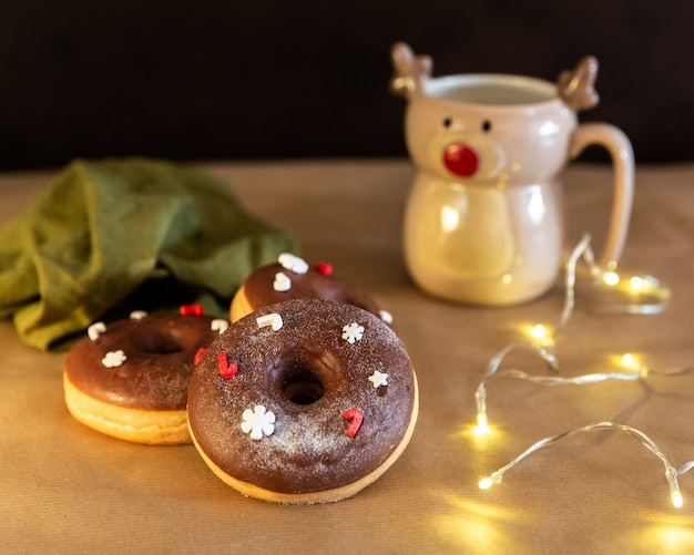 Christmas breakfast table with chocolate donuts decorated red and white sprinkles with hot cocoa in deer mug