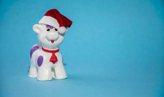 Christmas bull or cow toy in red new year hat and red bell on the neck as symbol of 2021 year