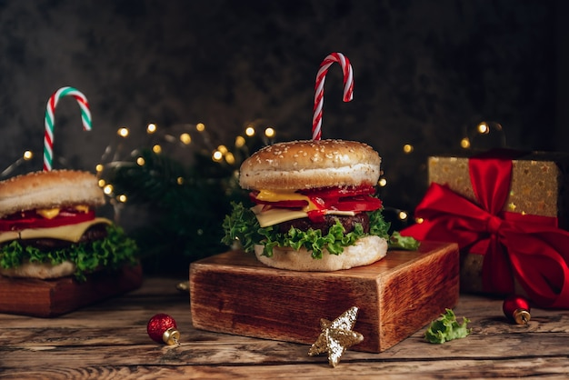 Christmas burger concept, with cande cane and christmas lights bokeh. dark background, selective focus