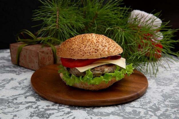 白い表面に対して白いテーブルにチーズ、トマト、レタスのクリスマスハンバーガー