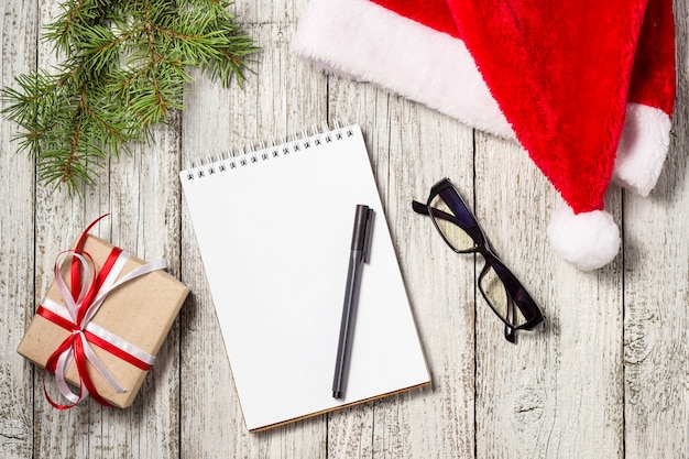 Christmas and business items with copy space cropped santa cap notepad pen glasses and decorated gift box and fir tree