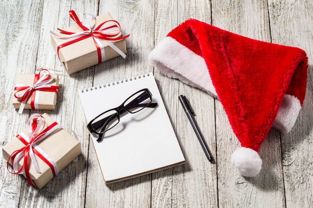 Christmas and business items with copy space santa cap notepad pen glasses and decorated gift boxes