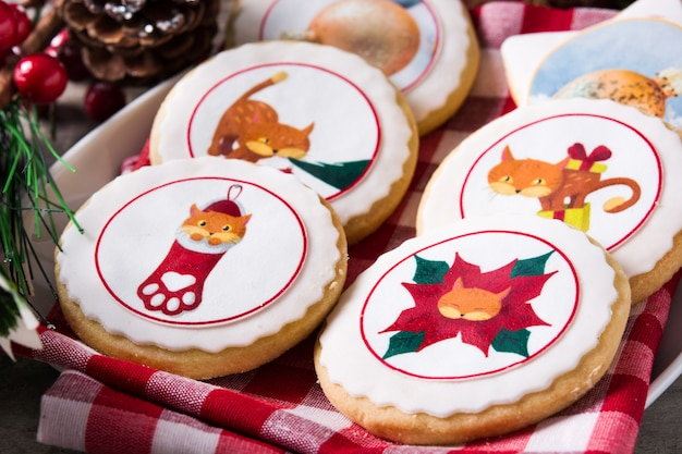 Christmas butter cookies decorated with christmas graphics, on wooden table close up