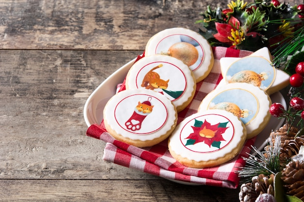 Christmas butter cookies decorated with christmas graphics, on wooden table copyspace