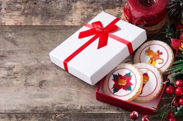 Christmas butter cookies decorated with christmas graphics, on wooden table, copyspace