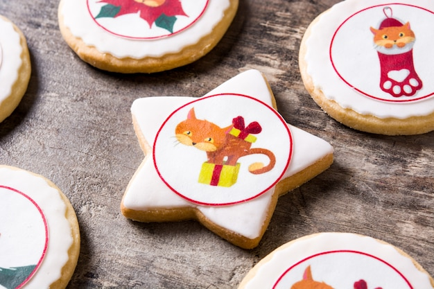 Christmas butter cookies decorated with christmas graphics on wooden table