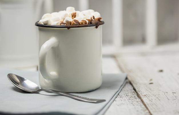 クリスマスカカオドリンク。灰色の壁に白いクリスマスマグカップにマシュマロとチョコレートカカオドリンク。伝統的な温かい飲み物、クリスマスまたは新年のお祝いカクテル
