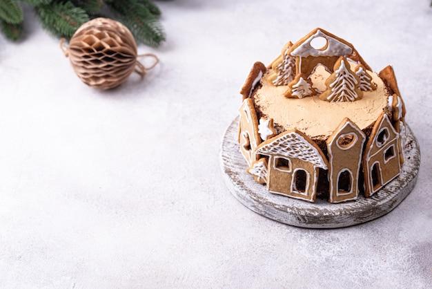 家の形をしたジンジャーブレッドクッキーで飾られたクリスマスケーキ