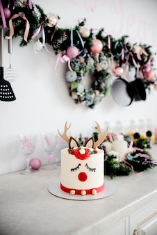 A christmas cake deer rudolph with red nose and christmas decorations. decorated kitchen.