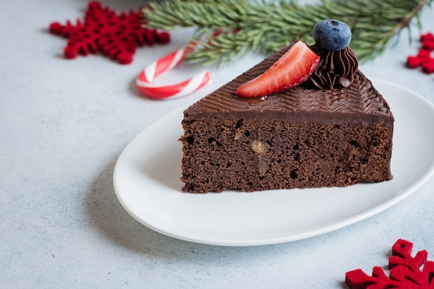 Christmas cake for dessert. delicious piece of chocolate cake with cup of coffee and milk on blue stone concrete table . breakfast food concept. festive holiday decoration