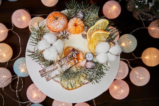 Рождественский торт на шоколадной основе с кремом, украшенный ягодами и фруктами