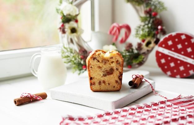 Christmas cake, milk, cocoa with marshmallows, cinnamon on plate