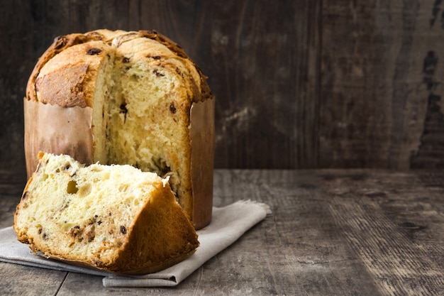 Christmas cake panettone on a rustic wooden, copy space