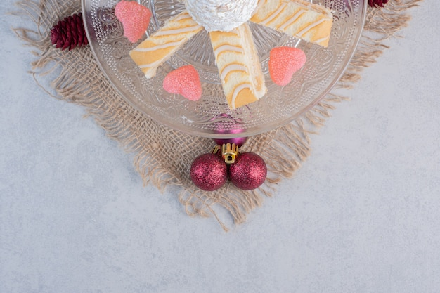 Christmas cake slices with heart shaped candies on glass plate.