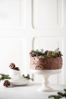 밝은 배경, 선택적 초점 이미지에 소나무 콘과 소나무로 장식 된 초콜릿 크리스마스 케이크