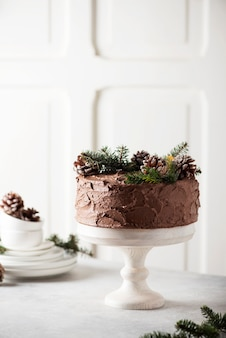 Christmas cake with chocolate decorated with pine cones and pine tree on light background, selective focus image