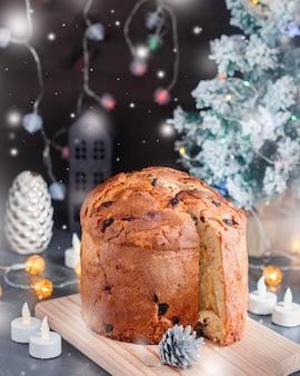 レーズンと砂糖漬けのフルーツとクリスマスの装飾とキャンドル、静物画のクリスマスケーキ