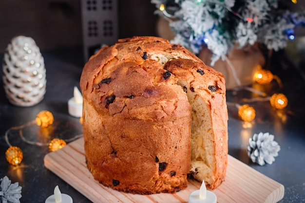 Christmas cake with raisins and candied fruit with christmas decor and candles, still life