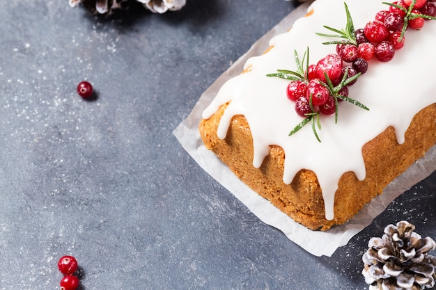 Christmas cake with sugar icing, cranberries and rosemary on a dark table. copy space