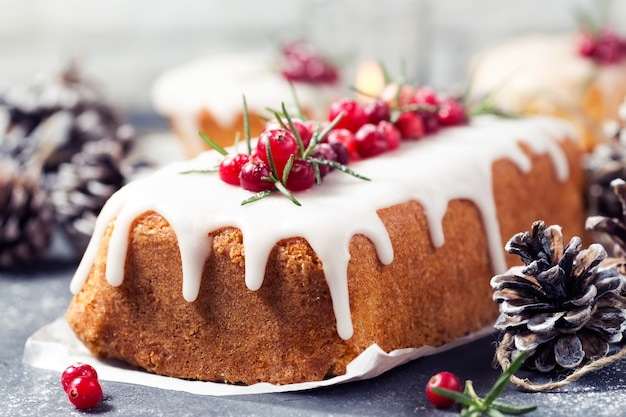 Christmas cake with sugar icing, cranberries and rosemary.
