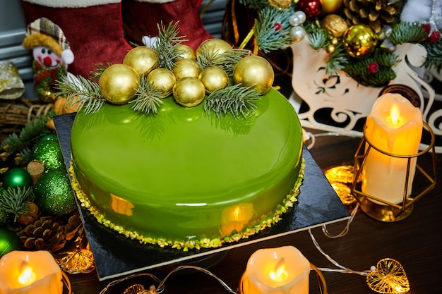 Christmas cake with tropical flavors on the background of candles, garlands, fir branches and cones
