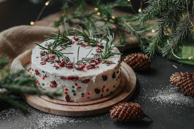 クランベリーとローズマリーで飾られた白いチーズクリームのクリスマスケーキ。