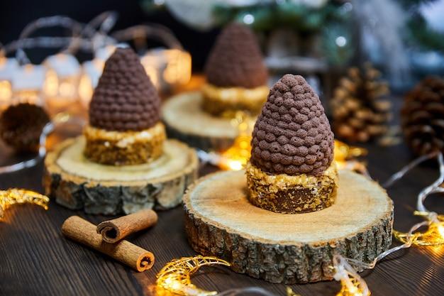 Рождественские торты в виде еловых шишек из шоколадной тарталетки и мусса со светящимися гирляндами
