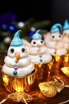 Рождественские торты в виде снеговиков на фоне светящихся гирлянд