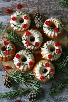白いアイシング、赤い果実、ローズマリーのクリスマスケーキ。