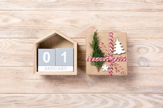 Рождественский календарь на 1 января. рождественский подарок, еловые ветки на деревянных белом фоне. копирование пространства, вид сверху.