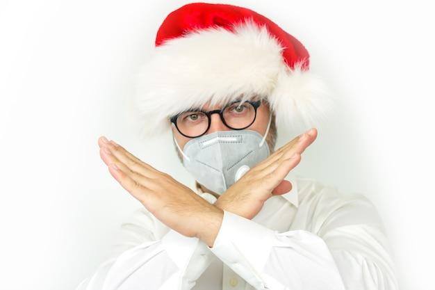 크리스마스 취소 개념, 남자 입고 크리스마스 모자와 그의 손으로 정지 신호를 보여주는 보호 마스크