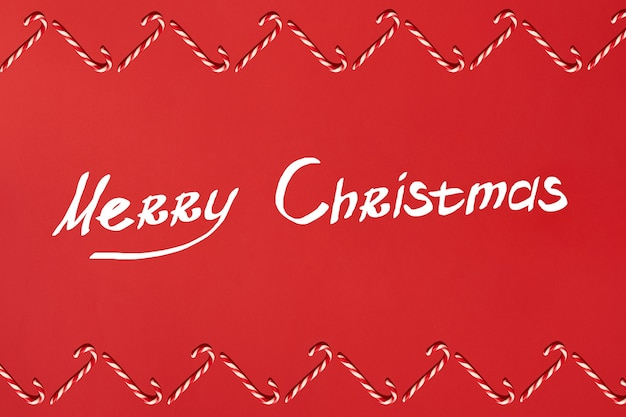 Рождественские конфеты трости граница на красном фоне плоская планировка и вид сверху