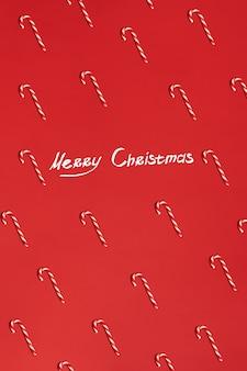 Рождественские конфеты трости на красном фоне плоская планировка и вид сверху