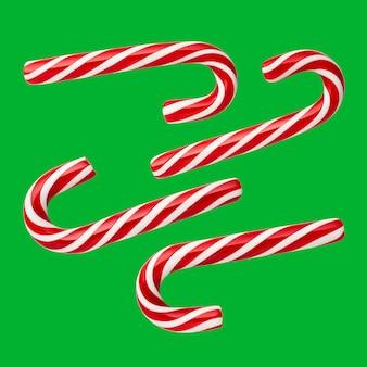 クリスマスキャンディー-手作りのペパーミントキャンディー杖。緑(クロマキー)の背景にお祝いのお菓子のセット