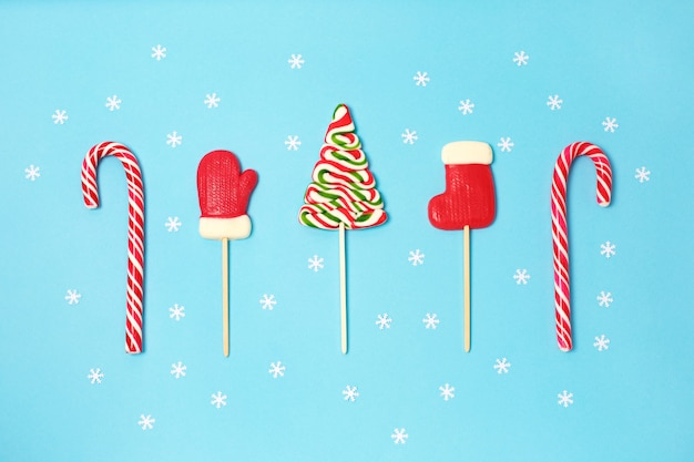 Christmas candies and little white snowflake on blue background.